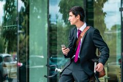 Young corporate employee holding a mobile phone while waiting ou. Tdoors in a modern European city stock images
