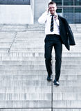 Young Corporate Man On Company Stairs. Young Corporate Man Talking On The Phone And Descending The Company Stairs Royalty Free Stock Photo