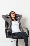 Young corporate woman relaxing or expressing laziness. Female self-employment - cool beautiful young corporate woman relaxing in an office chair resting or stock photography