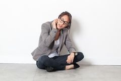 Young corporate woman talking on her cell phone on the floor Stock Photography