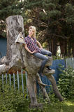Young country girl sitting on large old stump. Blonde young country girl sitting on large old stump Stock Photos