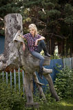 Young country girl sitting on large old stump. Blonde young country girl sitting on large old stump Royalty Free Stock Images