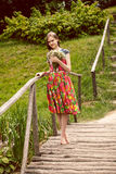 Young country girl smelling field flowers on wooden bridge Royalty Free Stock Images