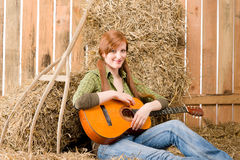 Young country woman play guitar in barn Royalty Free Stock Photo