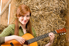 Young country woman playing guitar in barn Royalty Free Stock Photo