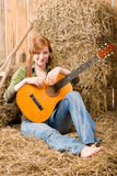 Young country woman sitting on hay with guitar Royalty Free Stock Image