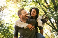 Young coupe in park. Boyfriend carrying his girlfriend on piggyback Royalty Free Stock Image