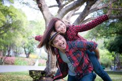 Young coupe in the park. Boyfriend carrying his girlfriend on pi stock photo