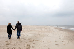 Young couple. Is walking on an empty beach Stock Images
