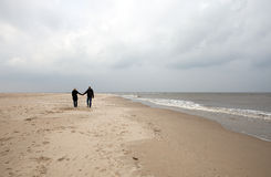 Young couple. Is walking on an empty beach Royalty Free Stock Images