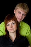 Young couple. Portrait of young couple against black background Stock Photos