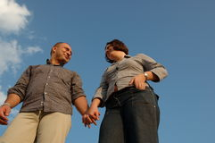 Young couple. A young couple standing against blue sky, holding each others hands Stock Photo