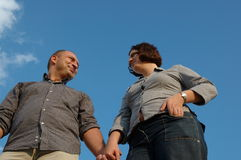 Young couple. Two young people standing against blue sky and looking in each others eyes Stock Image