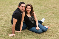 Young Couple. Young married couple in a loving pose sitting on a lawn in a park Stock Image
