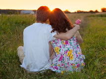 The Young Couple. Young couple sitting back to camera on the grass and looking at sunset royalty free stock photo