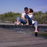 Young couple. A  portrait of a young caucasian couple  hugging and kissing seated on a pontoon Royalty Free Stock Photo