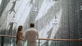 Young couple admired Waterfall in Dubai Mall.  stock video