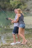 Young couple angling standing on river shore. Young royalty free stock photo