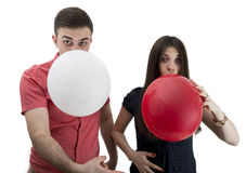 Young couple announcing their baby while blowing balloons Royalty Free Stock Photography