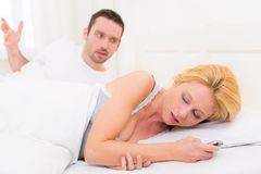 Young couple arguing on a bed cause of texts Royalty Free Stock Photo