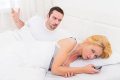 Young couple arguing on a bed cause of texts. View of Young couple arguing on a bed cause of texts Stock Photography