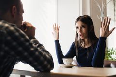 Young couple arguing in a cafe. Relationship problems. Royalty Free Stock Photos