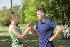 Young couple arguing while sitting on bench in park. Problems in relationship stock image