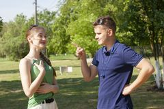 Young couple arguing while sitting on bench in park. Problems in relationship royalty free stock photo