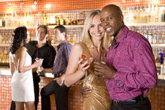 Young couple arm in arm in bar with drinks, smiling, portrait Stock Images