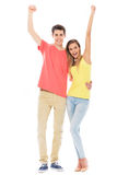 Young couple with arms raised Royalty Free Stock Images