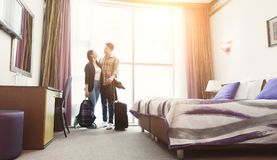 Young couple arrived to hotel room on honeymoon. Young happy couple arrived to hotel room on honeymoon. Family standing on window background royalty free stock photo