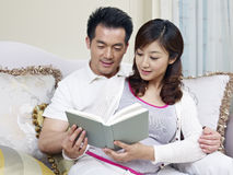 Young couple. Young asian couple reading a book together Stock Photography