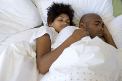 Young couple asleep in bed, elevated view Royalty Free Stock Photo