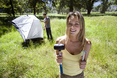 Young couple assembling dome tent on camping trip in woodland clearing, focus on woman holding tent peg and mallet in foreground,  Royalty Free Stock Photos