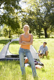 Young couple assembling dome tent on camping trip in woodland clearing, focus on woman, portrait Stock Photography