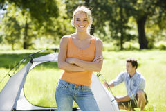 Young couple assembling dome tent on camping trip in woodland clearing, focus on woman, portrait Stock Image