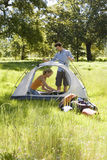 Young couple assembling dome tent on camping trip in woodland clearing, side view Royalty Free Stock Images