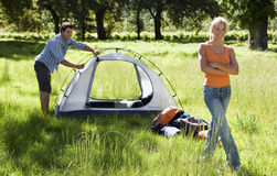 Young couple assembling tent on camping trip in woodland clearing, woman smiling, arms folded, portrait Royalty Free Stock Images