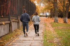 Young couple, athletes, train in the autumn park, jog. Royalty Free Stock Images