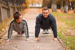 Young couple, athletes, train in the autumn park, stand in the bar Stock Photography