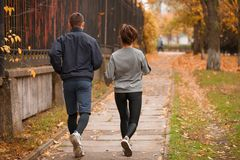Young couple, athletes, train in the autumn park, jog. Stock Photography