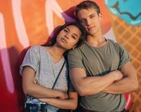 Young couple with attitude standing by a wall of graffiti. Portrait of a young couple with attitude standing sidy by side with their arms crossed in front of a stock image