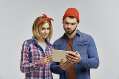 Young couple with attractive looks in casual hipster clothes look attentively at the tablet and learn something. Stock Photo