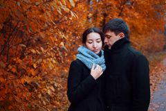 Young couple in autumn Park. Cute guy and a girl walking together Royalty Free Stock Image