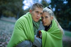 Young couple in autumn park in gloomy day Stock Photos