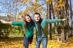 Young couple in autumn park on a sunny fall day Stock Photography