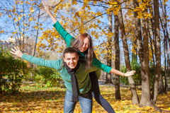 Young couple in autumn park on a sunny fall day Stock Images