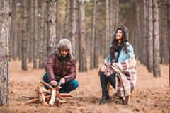 Couple in the forest. A girl is sitting covered in a blanket, the guy sharpens wooden knives. stock photos