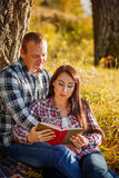 Young couple in autumn wood at picnic and reading book. Stock Photo