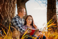 Young couple in autumn wood at picnic and reading book. Stock Images